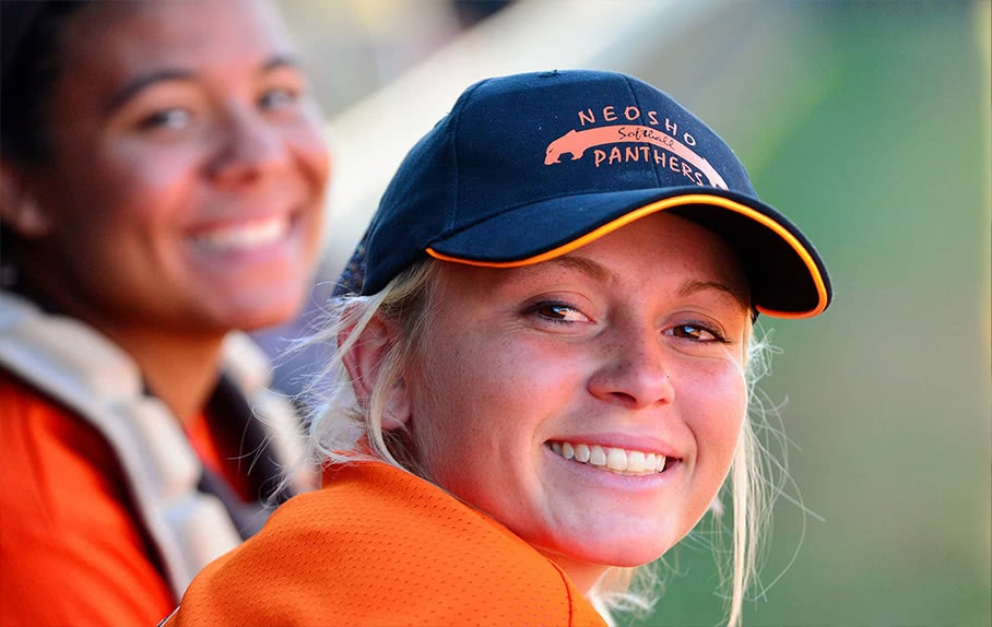 An up-close portrait shot of a smiling softball player
