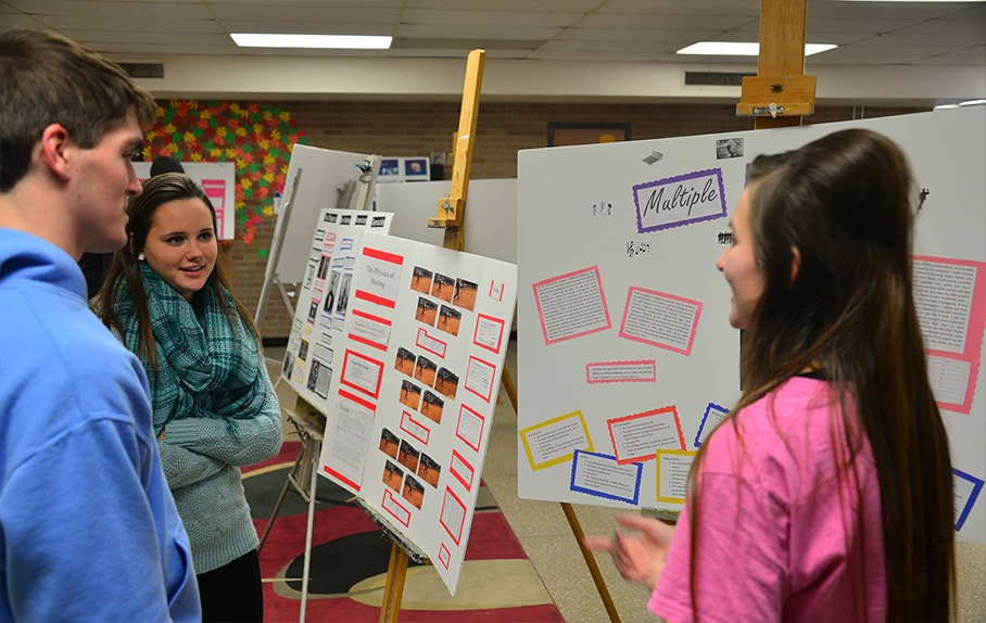 Students talking in front of poster board presentations