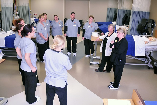Group of nursing students listening to an instructor talk